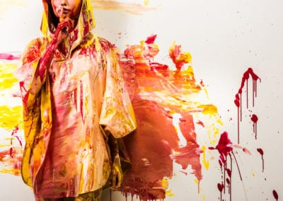cropped image of woman in raincoat painted with yellow and red paints showing silence gesture