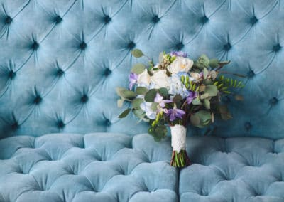 A beautiful multicolored wedding bouquet with wildflowers and roses lies against the blue sofa.
