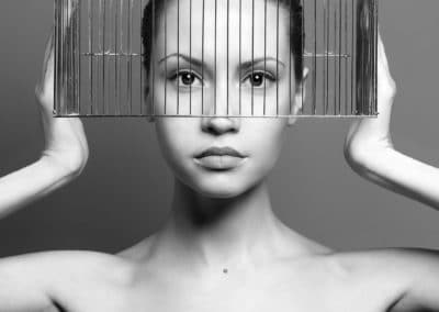Surrealistic portrait of young lady with cage