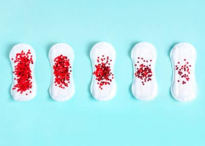 Menstrual pads with red glitter on colored background