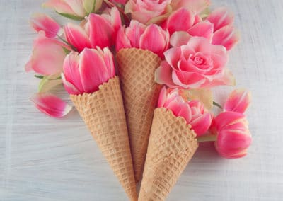 sweet ice cream cone with pink tulip flowers on white wood background